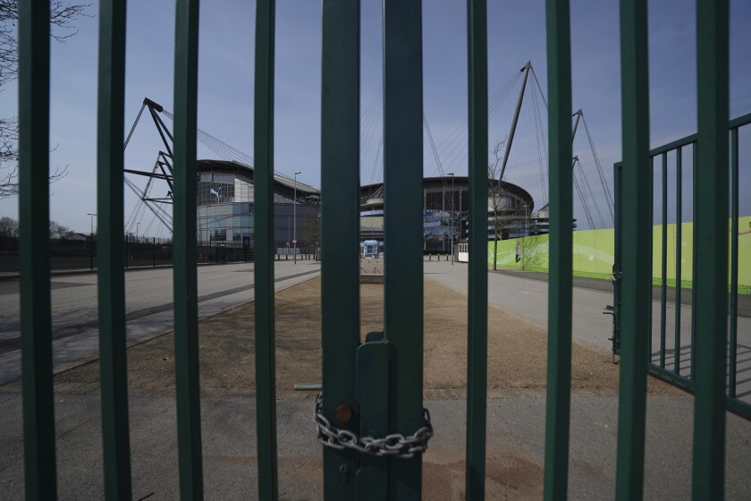 FILE - In this file photo dated Thursday, April 9, 2020, gates stand locked outside the closed English Premier League soccer Manchester City Etihad Stadium, in Manchester, northern England. Guidance for sports bodies was published by the government on Saturday May 30, 2020, as COVID-19 lockdown restrictions are being eased further, allowing Sports events to resume in England from upcoming Monday, without any spectators and providing they comply with the government's coronavirus protocols. (AP Photo/Jon Super, FILE)