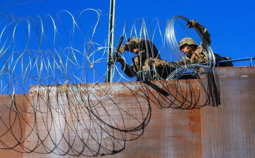 US military soldiers install barbed wire on the border with Mexico as seen from Colonia Libertad in Tijuana, Mexico, 12 November 2018. Around 4,000 migrants departed in the morning from Irapuato, in the central state of Guanajuato, to Guadalajara, about 252 kilometers away, on their way to the US border. EPA-EFE/FILE/JOEBETH TERRIQUEZ
