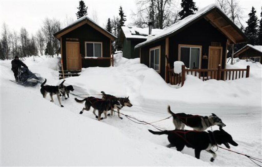 Robert Bundtzen drives his team past cabins at Winterlake Lodge at the Finger Lake checkpoint in Alaska during the Iditarod Trail Sled Dog Race on Monday, March 4, 2013. (AP Photo/The Anchorage Daily News, Bill Roth)