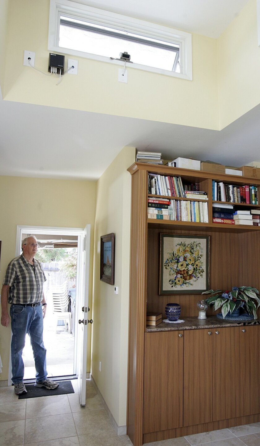 Bruce Haupt stands in the back doorway of his Mira Mesa home, not far from a solar chimney, which directs heat upward and outward resulting in a flow of air into the home.| John Gastaldo/Union-Tribune
