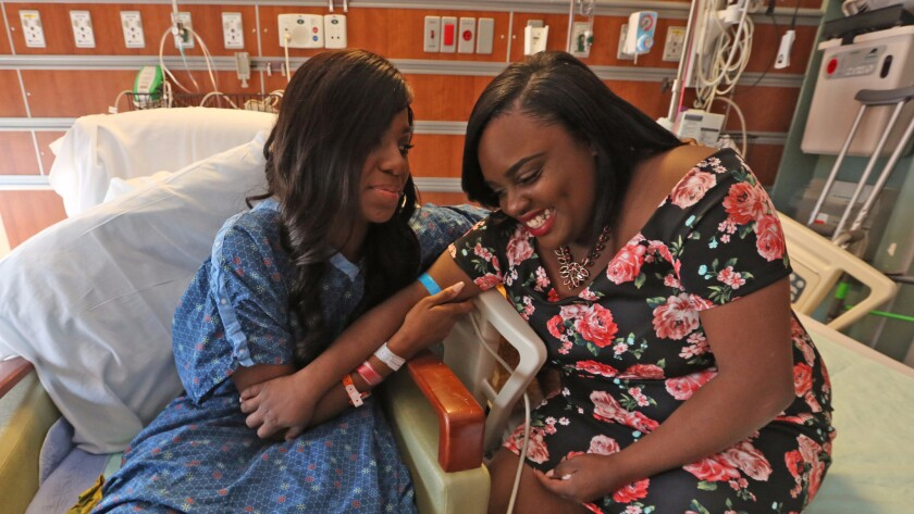 Tiara Parker, right, and Patience Carter, both wounded in the Pulse nightclub shooting, share a moment in the hospital.