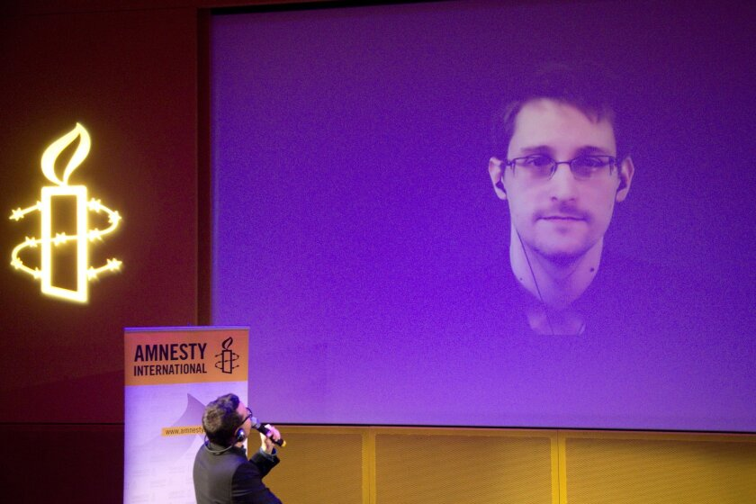 FILE - In this Dec. 10, 2014, file photo, former U.S. National Security Agency contractor Edward Snowden, who is in Moscow, is seen on a giant screen during a live video conference for an interview as part of Amnesty International's annual Write for Rights campaign at the Gaite Lyrique in Paris, France. Domestic digital spying on ordinary citizens is an international threat that will only be slowed with measures like a proposed international treaty declaring privacy a basic human right, Snowden said Thursday, Sept. 24, 2015, in a video appearance at a Manhattan forum. (AP Photo/Charles Platiau, Pool, File)