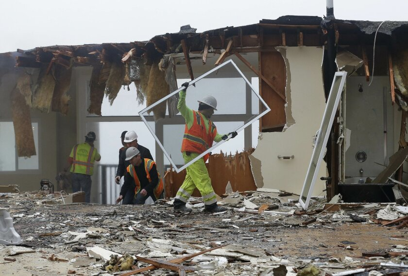 A work crew demolishes a home that is sliding off a hill and threatening another home in San Francisco, Friday, Jan. 29, 2016. City crews ordered an emergency demolition on Thursday and the work continued Friday. (AP Photo/Jeff Chiu)