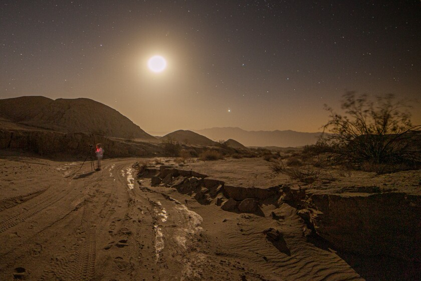 A hiker pauses to take a night photo in the desert. There is a surprising amount of light when the moon is full.