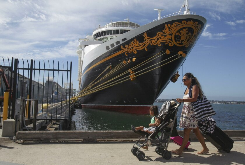 A family rolls luggage along the Embarcadero as they head to the dock to board the Disney Cruise Line ship in San Diego. By the end of this year, its 2,700-passenger Disney Wonder will have made 10 calls in San Diego, many of them sailings to Ensenada and Cabo San Lucas.