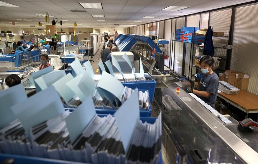 A worker runs mail-in-ballots through a sorting machine