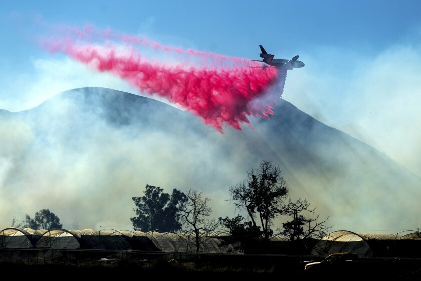 An air tanker drops retardant as the Maria Fire approaches Santa Paula, Calif., on Friday, Nov. 1, 2019. According to Ventura County Fire Department, the blaze has scorched more than 8,000 acres and destroyed at least two structures. (AP Photo/Noah Berger)