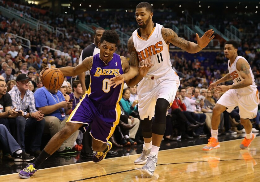 Lakers guard Nick Young tries to drive past Suns forward Markieff Morris in the first half Monday night in Phoenix.