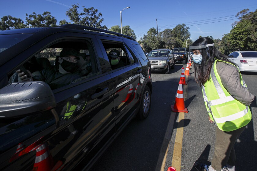 A woman in a yellow safety vest with a face shield speaks to a masked driver in a line of waiting cars.