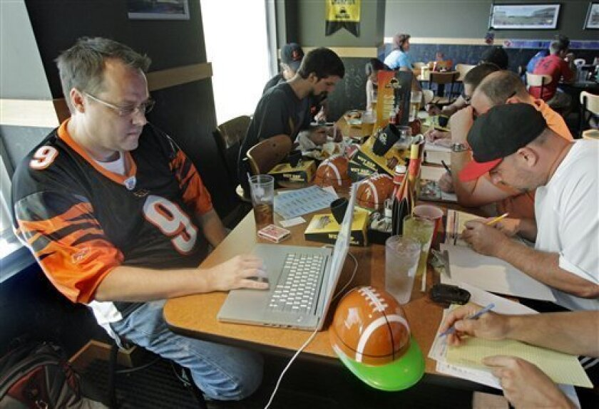 In this Aug. 30, 2010 photograph, Brian Sherman, left, uses his laptop to record moves in his team's fantasy football draft, at a Buffalo Wild Wings restaurant in Cincinnati. Some restaurant chains around the country have launched promotional drives to score with dedicated players of the growing pa