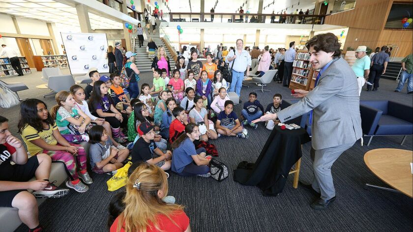 A magician entertains school childrent at the Glendale Downtown Central Library at the celebration o