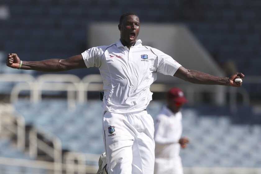 FILE - In this Aug. 30, 2019, file photo, West Indies' captain Jason Holder celebrates taking the wicket of India's captain Virat Kohli during day one of the second Test cricket match at Sabina Park cricket ground in Kingston, Jamaica. The West Indies cricket team departed from Antigua on Monday, June 8, 2020 for a three-test tour of England with the entire touring party based in the Caribbean having returned negative tests to COVID-19. (AP Photo/Ricardo Mazalan, File)