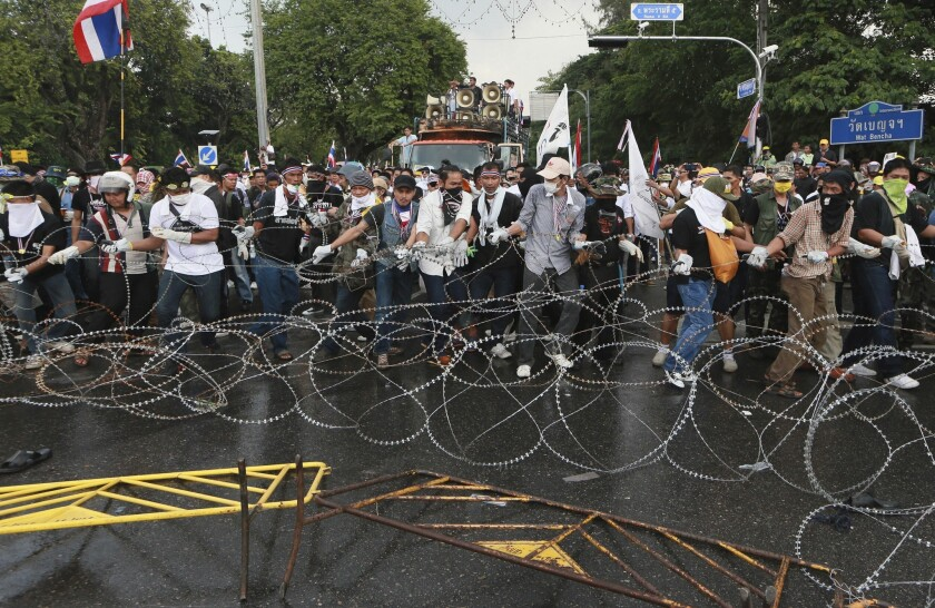 Anti-government protesters try to remove barbed wire set up by riot police during a rally in Bangkok, Thailand.