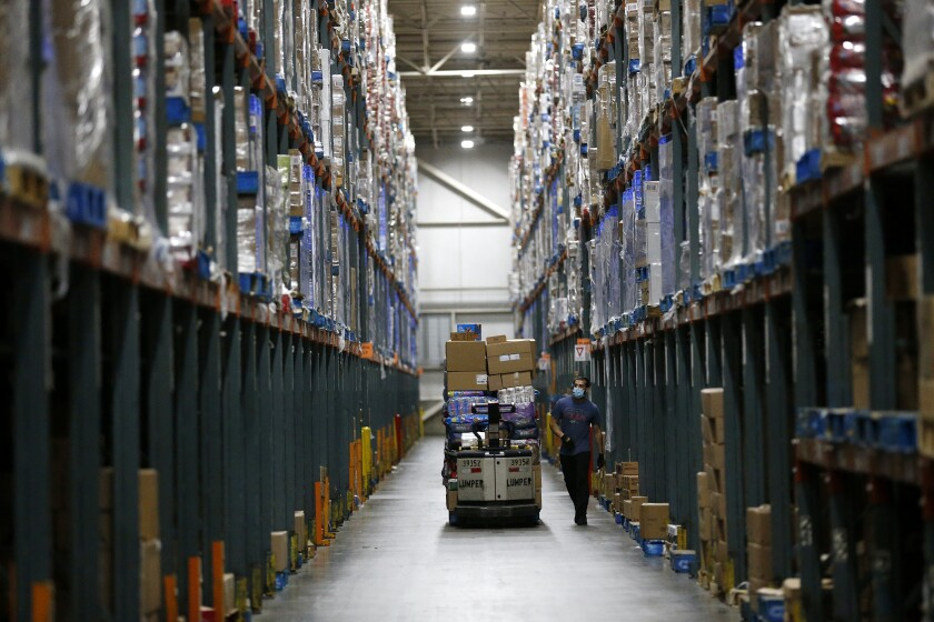 Associates fill orders for Ralphs and Food 4 Less grocery stores at the Ralphs Distribution Center in Riverside.