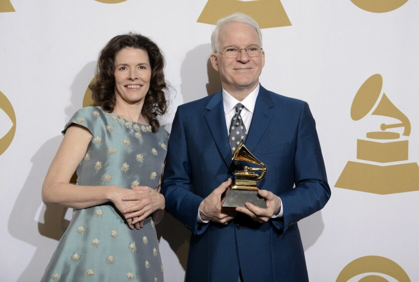 """Edie Brickell, left, and Steve Martin pose in the press room with the award for best American roots song, """"Love Has Come For You,"""" at the 56th annual Grammy Awards at Staples Center on Sunday, Jan. 26, 2014, in Los Angeles. (Photo by Dan Steinberg/Invision/AP)"""