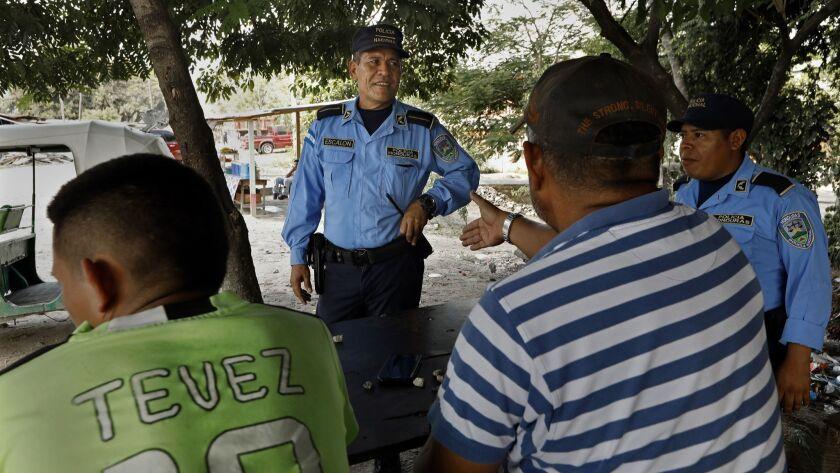 BORDO DEL RIO BLANCO, HONDURAS--NOV.7, 2018--Police officer Domingo Escalón, age 50, (center) was t