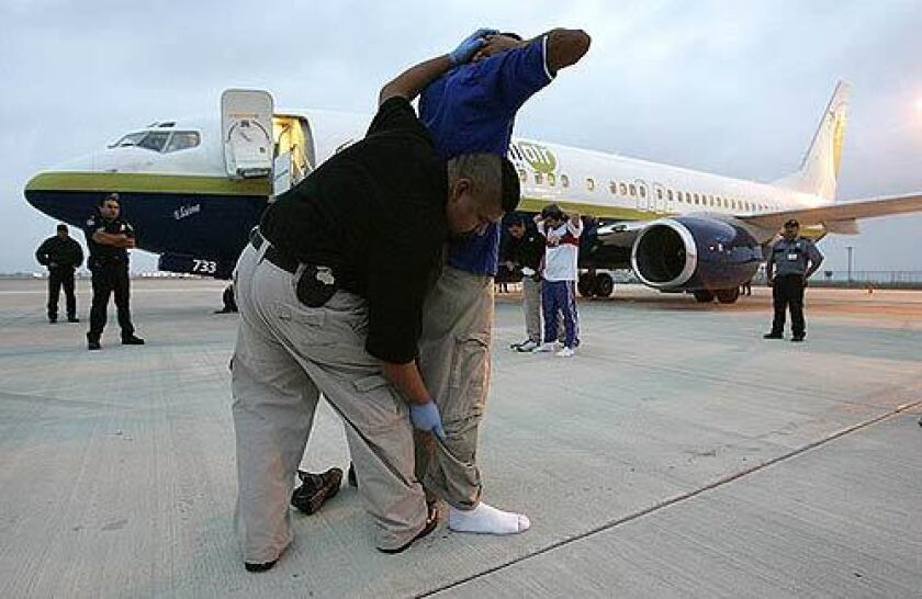 Immigration and Customs Enforcement agents search undocumented immigrants before placing them aboard a plane that will take them back to El Salvador.