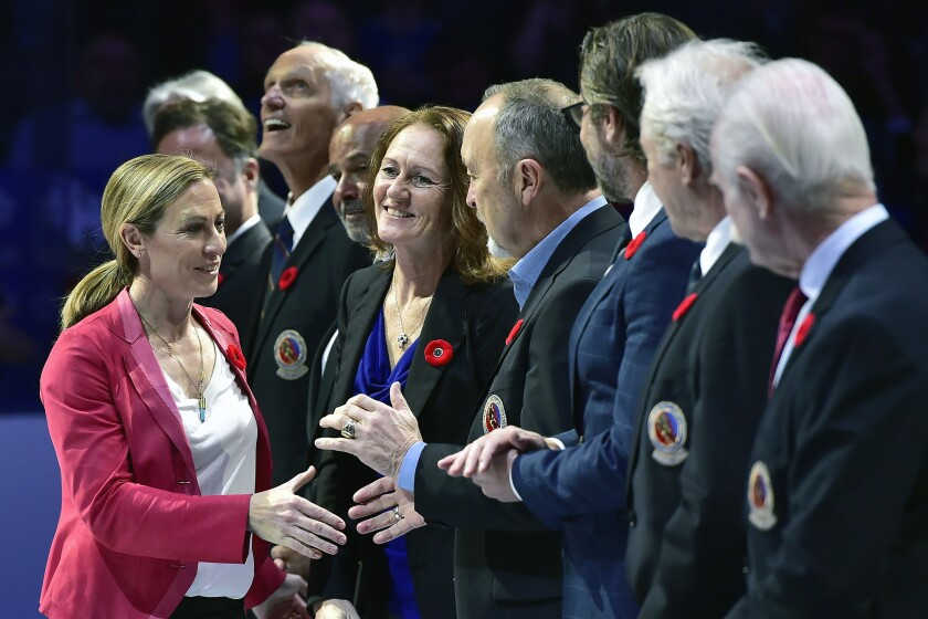 """FILE - In this Nov. 9, 2018, file photo, Hockey Hall of Fame inductee Jayna Hefford shakes hands with people associated with the hall before a hockey game between the Toronto Maple Leafs and the New Jersey Devils in Toronto. The Professional Women's Hockey Players' Association is forging ahead in its bid to establish an economically sustainable professional league in North America with or — for now — without the NHL's full financial backing. In response to Sportsnet.ca reporting the NHL was not in a position to operate a women's league for the foreseeable future, PWHPA executive Jayna Hefford wrote in an email to The Associated Press late Thursday that her group has begun developing what she called """"a parallel path for a future that doesn't rely on NHL support."""" (Frank Gunn/The Canadian Press via AP, File)"""