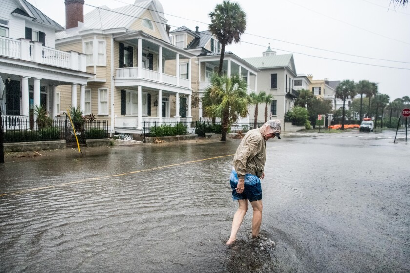Bill Olesner walks down a flooded South Battery Street in Charleston, S.C., while cleaning debris from storm drains.