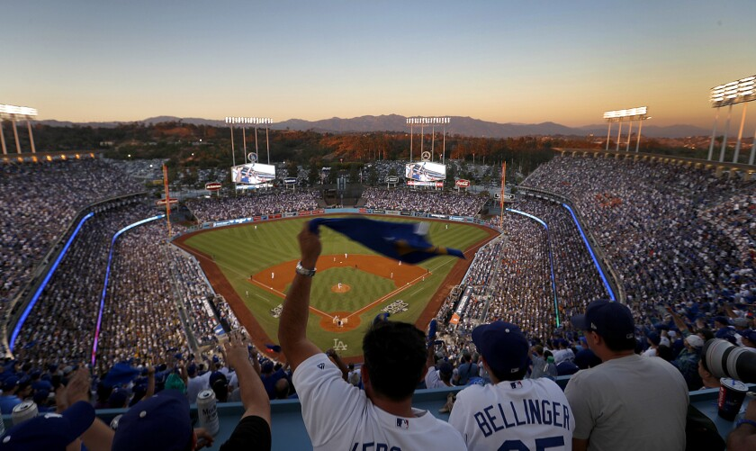 Dodgers fans wave souvenir towels as they cheer on the Dodgers from the top deck section during Game 2 of the World Series at Dodger Stadium.