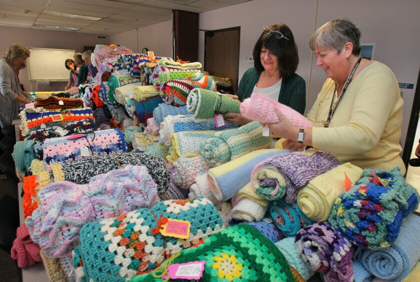 At the Escondido offices of North Inland Child Welfare Services on Tuesday, Sherry Metz (left) and Chris Bodle stack hand-made blankets that were made by volunteers for foster children.