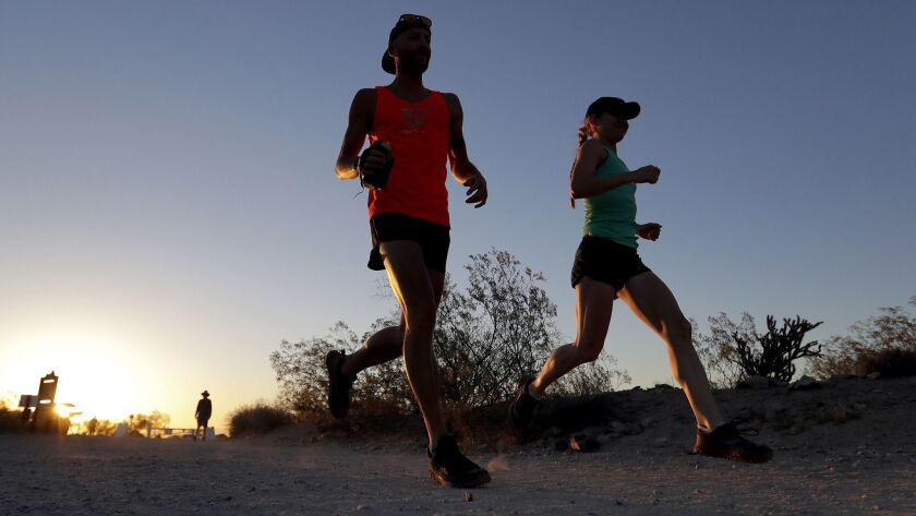 A couple runs through section of South Mountain Park at sunrise to avoid the excessive heat, Friday,