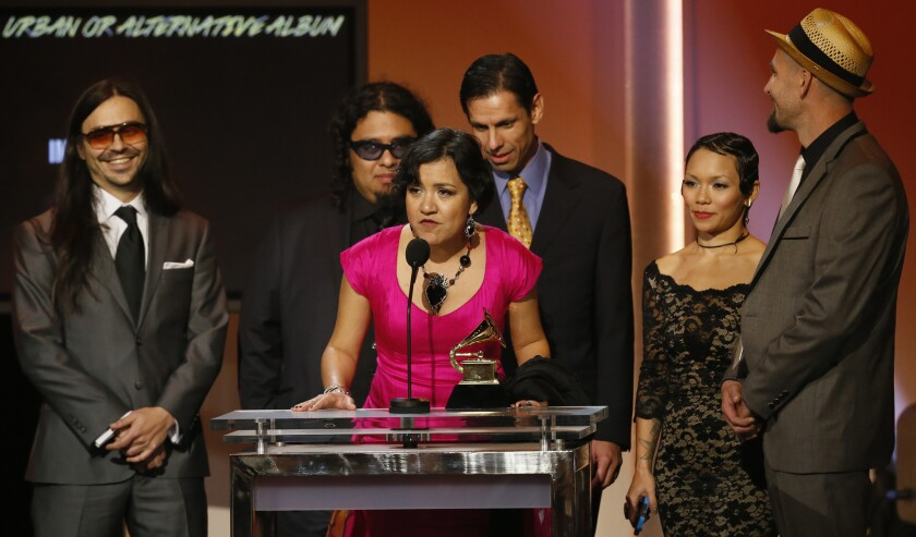 Martha Gonzalez, in pink, and members of Quetzal accept a Grammy for Latin rock, urban or alternative album in 2013.