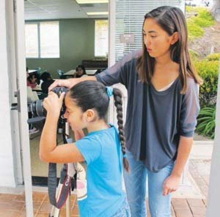 Shannon Blue, left, works with a student in the Outside the Lens program. Photo: Courtesy