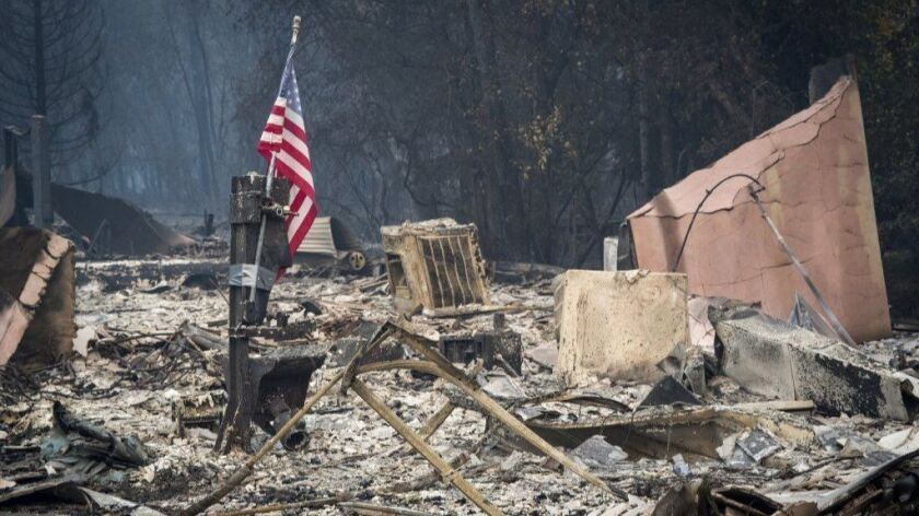 An American flag stands among burned rubble in Paradise, Calif., on Nov. 13.