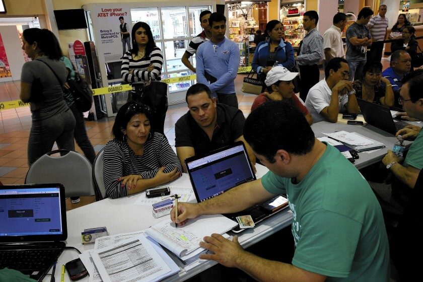 Denis Garcia of Sunshine Life and Health Advisors helps Marlene Lima-Rodriguez, left, and Javier Gonzalez buy health insurance under the Affordable Care Act, as other wait their turn, at the Mall of Americas in Miami.