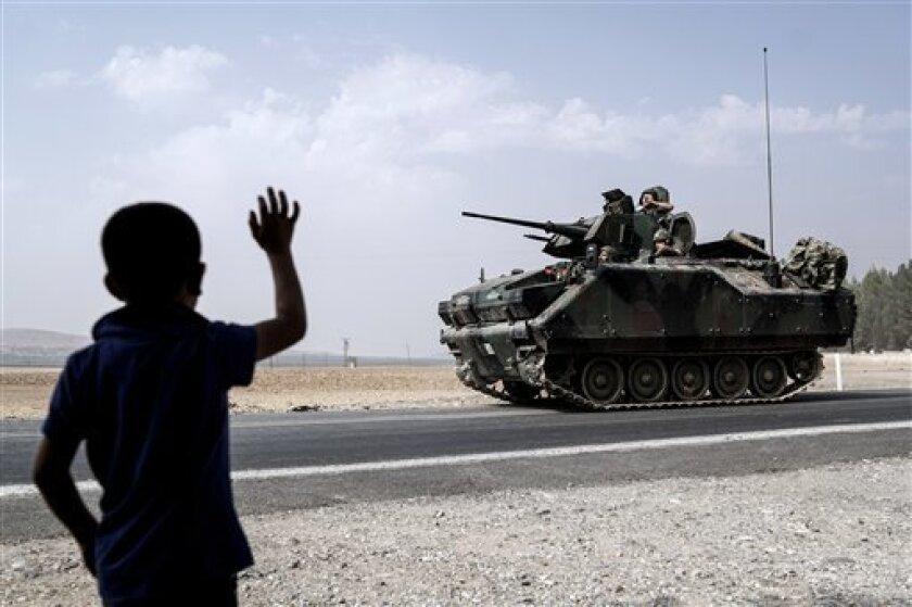 Un niño saluda a tropas turcas que viajan hacia la frontera siria en Karkamis, Turquía, el viernes 26 de agosto de 2016.