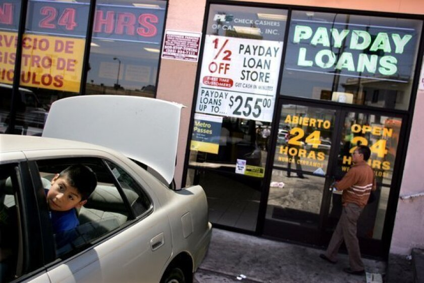 A customer walks inside a Payday Loan Store in Los Angeles while a child watches his father work on their car.