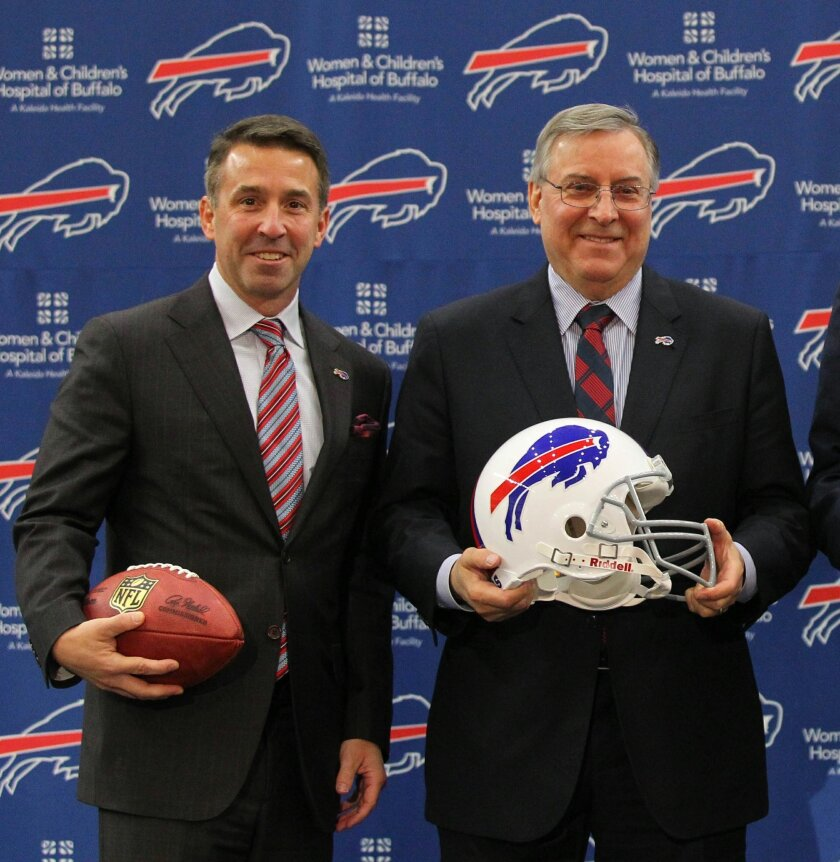 FILE - In this Jan. 14, 2015, file photo, Buffalo Bills team president Russ Brandon, left, and owner and CEO Terry Pegula pose at an NFL football press conference in Orchard Park, N.Y. Bills president Russ Brandon's role is expanding to include overseeing the NHL's Buffalo Sabres as part of a front-office restructuring under Terry and Kim Pegula, who own both teams. Brandon will assume the duties of Sabres president Ted Black, who reached a mutual agreement to part ways with the franchise, the team announced Monday. (AP Photo/Bill Wippert, File)