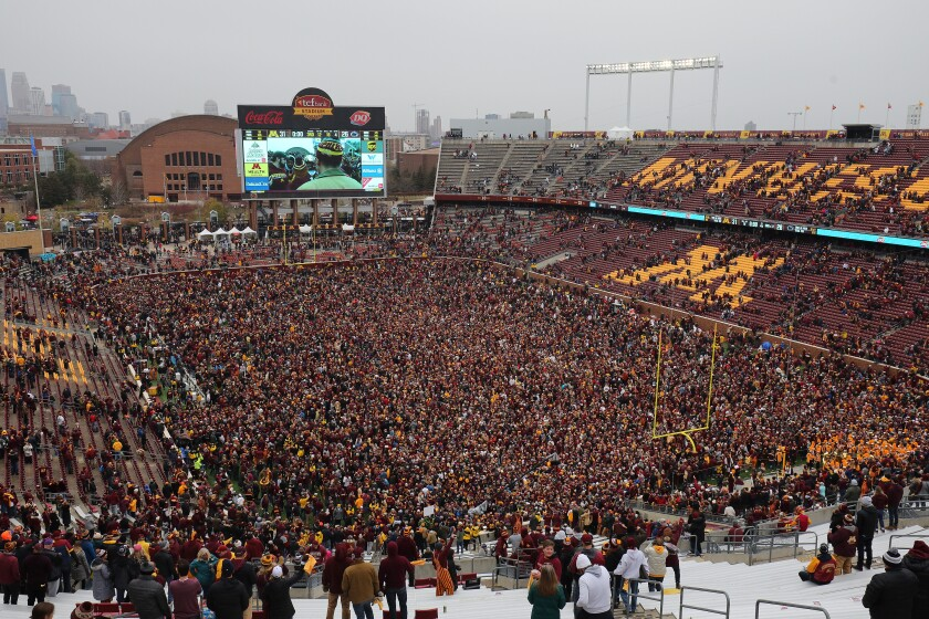 Minnesota fans storm the field after the Gophers beat Penn State