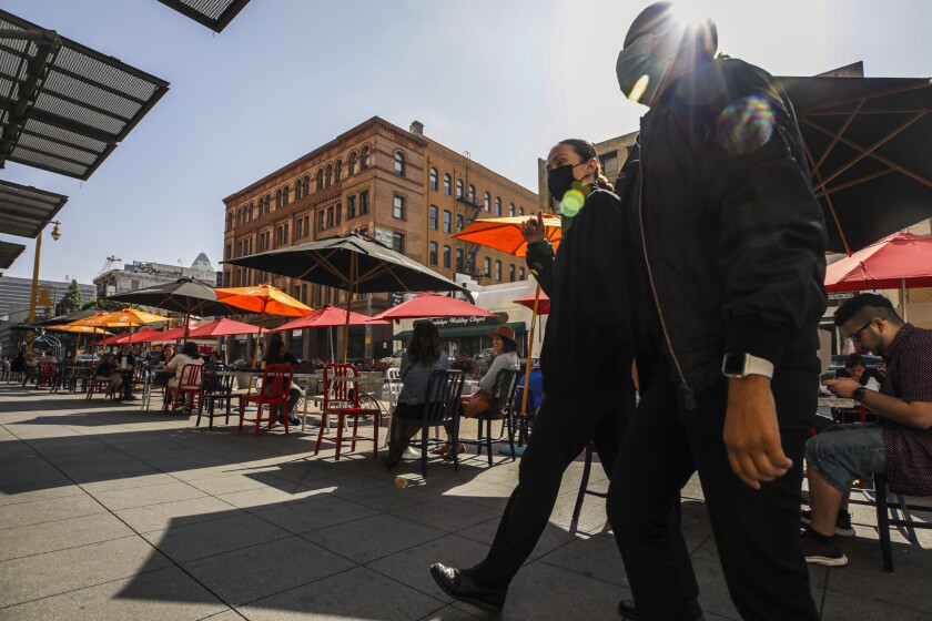 Two masked men walk past patrons eating at tables covered with umbrellas in the Central Market in downtown Los Angeles.