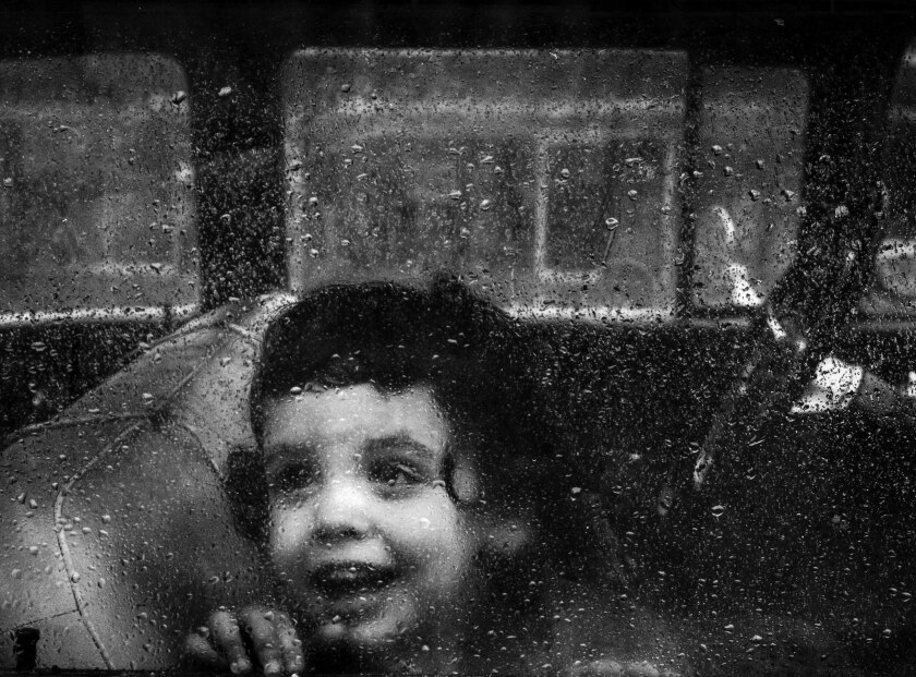 Los Angeles Times staff photographer Mary Frampton took this 1963 photo of a little girl peering out