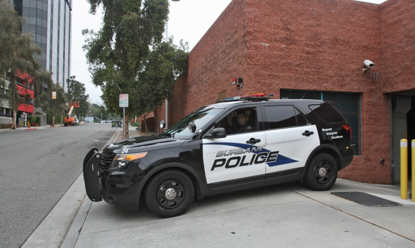 A Burbank police vehicle exits the underground parking garage at police headquarters on April 8.