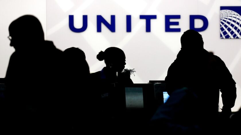 FILE - In this Saturday, Dec. 21, 2013, file photo, Holiday travelers check in at the United Airline