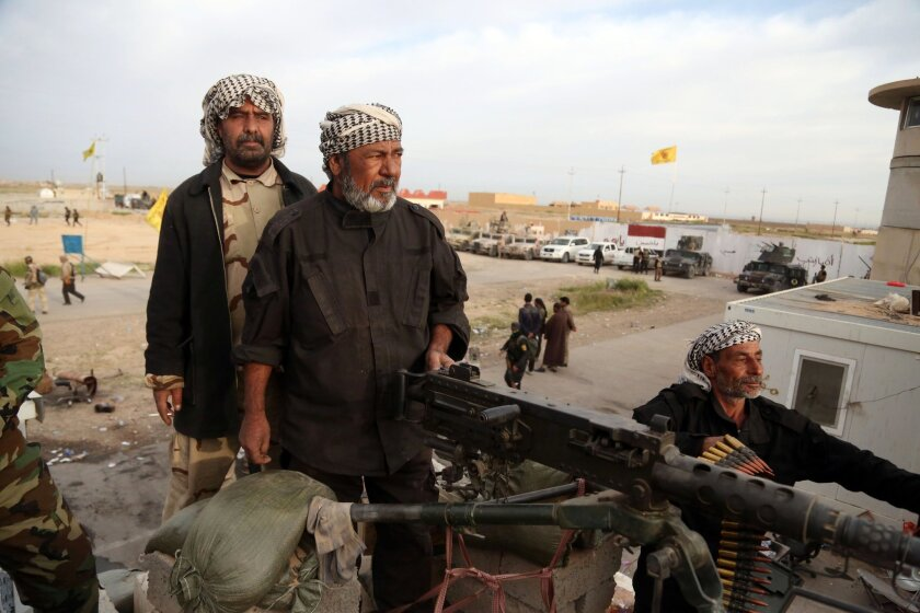 Shiite Muslim militiamen take combat positions at the front line in Tikrit, Iraq, on March 12.