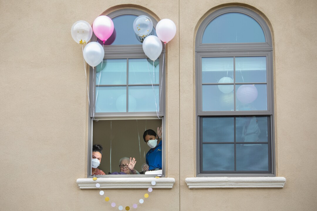 Margaret Jones, center, waves from her room at an assisted living facility in Redondo Beach as she celebrates her 91st birthday.