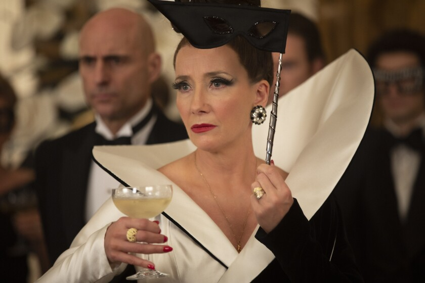 Emma Thompson as the Baroness holds a wine glass and a mask with a man in a tuxedo behind her.