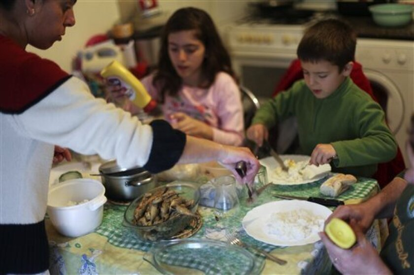 In this photo taken on March 29, 2013, Elena Baptista, left, serves a meal to her daughter Vania, 12, left, son Joao, 7, and husband Pedro, partially seen on the right, in their house's kitchen/living room in Loures, outside Lisbon. The Baptista family counts itself among the casualties of an unrel