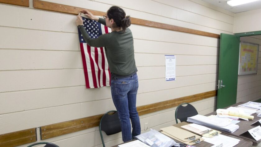 Election poll worker Kesia Estrada hangs the American flag correctly on the wall as she helps set up the polling station at the Colina del Sol recreation center on June 5 for San Diego's primary election.
