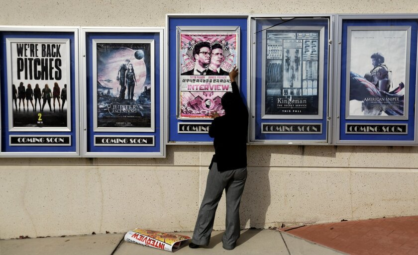 "A poster for the movie ""The Interview"" is taken down by a worker after being pulled from a display case at a Carmike Cinemas movie theater, Wednesday, Dec. 17, 2014, in Atlanta. Georgia-based Carmike Cinemas has decided to cancel its planned showings of ""The Interview"" in the wake of threats agains"