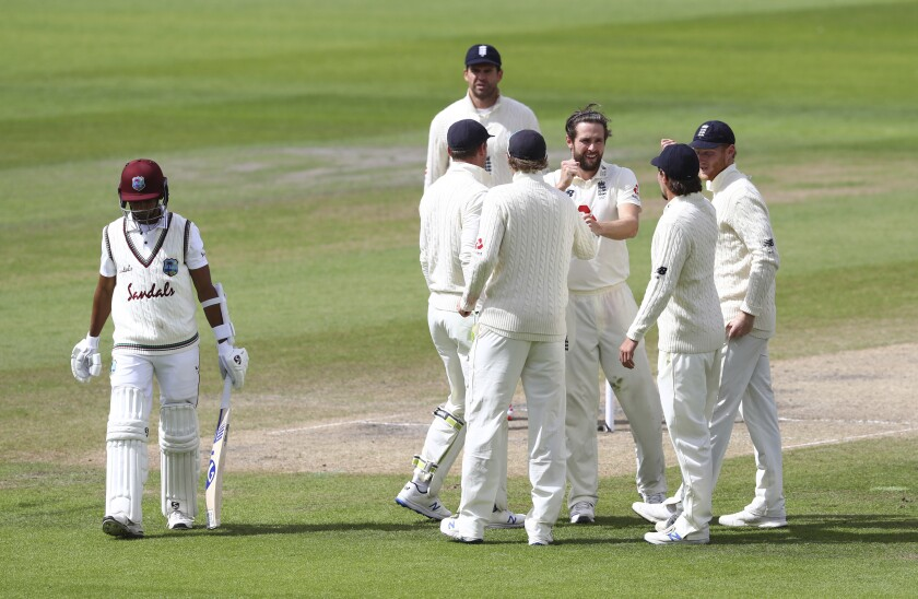 England's Chris Woakes, third right, celebrates with teammates the dismissal of West Indies' Shane Dowrich, left, during the fifth day of the third cricket Test match between England and West Indies at Old Trafford in Manchester, England, Tuesday, July 28, 2020. (Michael Steele/Pool via AP)