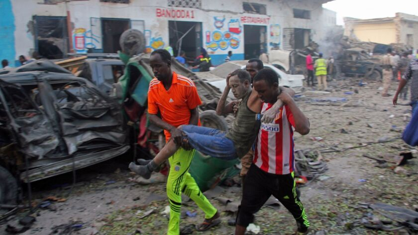 Somalis carry away a man injured when a car bomb exploded outside a hotel in Mogadishu, Somalia, on Oct. 28, 2017.