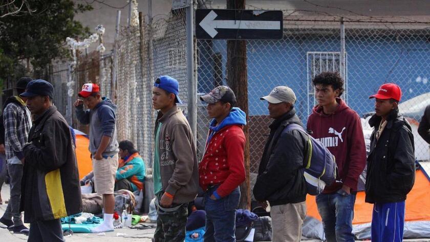Un grupo de migrantes centroamericanos hace fila para recibir comida en un refugio en Tijuana, México.