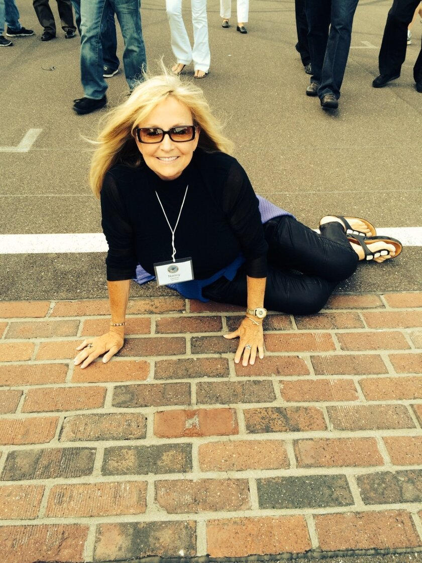 La Jolla-resident Nancy Gardner prepares to kiss the bricks at Indianapolis Motor Speedway while visiting that area to attend the 2014 FBI National Citizens Academy Alumni Association National Leadership Conference.