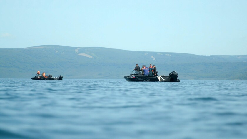 Rescue workers in boat on lake
