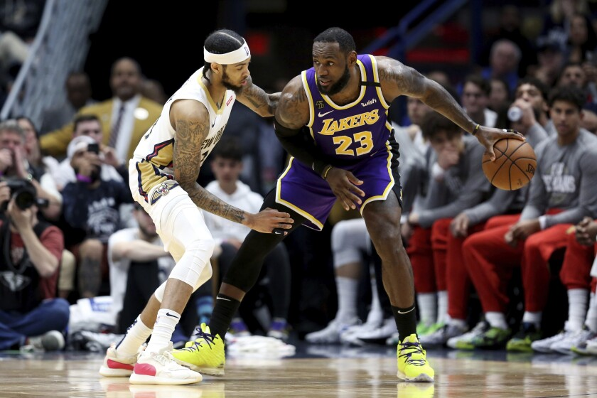Lakers star LeBron James dribbles next to New Orleans Pelicans forward Brandon Ingram during the Lakers' win Sunday.